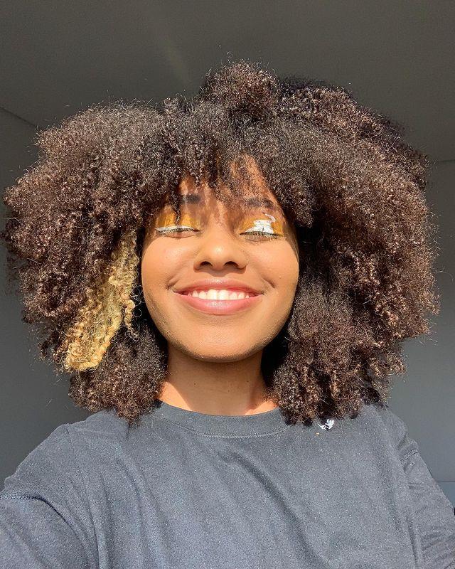 Selfie de uma mulher sorrindo. Ela usa uma camiseta preta e cabelo crespo solto.