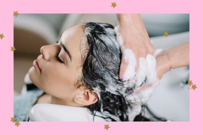 Pessoa lavando o cabelo de uma jovem. Na imagem vemos as mãos esfregando o cabelo e espuma.