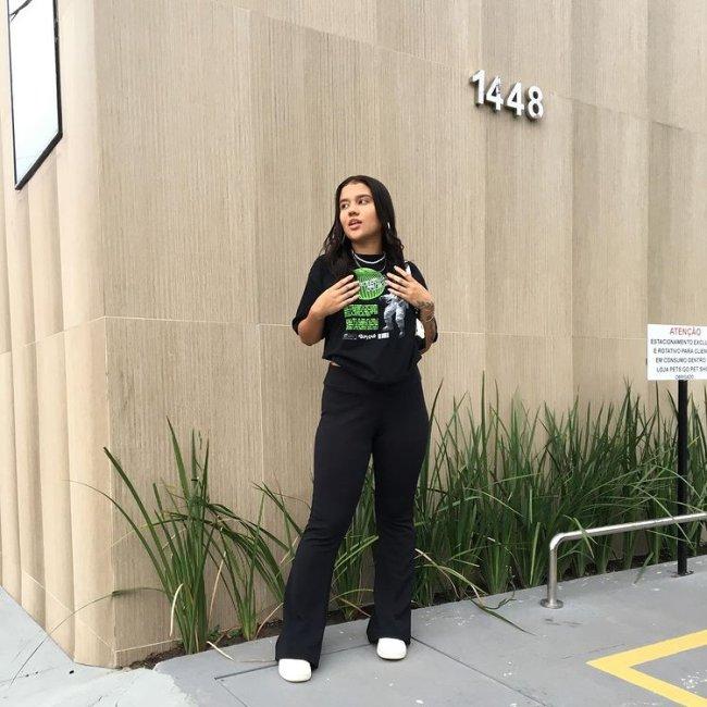 Jovem posando em frente a parede bege e detalhe de plantas na parte inferior, ela usa camiseta preta com detalhes em verde e calça bailarina. Ela olha para o lado com uma expressão séria.