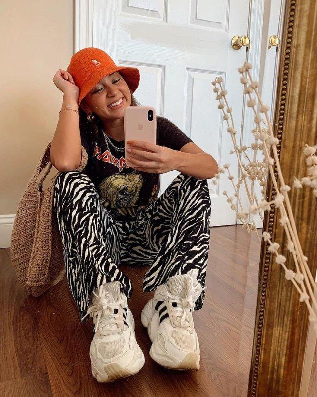 Jovem tirando foto em frente a espelho, ela está sentada e usa bucket hat laranja, camiseta de banda e calça de zebra com tênis branco.