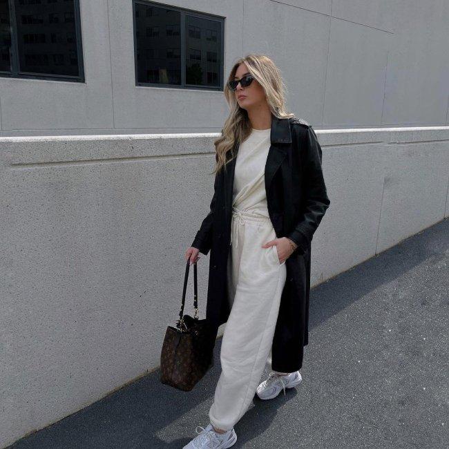 Jovem posando na rua com conjunto monocromático e sobretudo preto. Uma de suas mãos está na bolso da calça e ela usa óculos escuros.