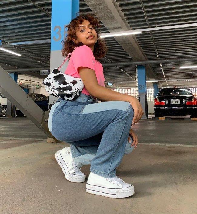 Jovem posa agachada no chão com expressão séria e usando blusa rosa com bolsa com estampa de vaquinha e calça jeans com tênis branco.