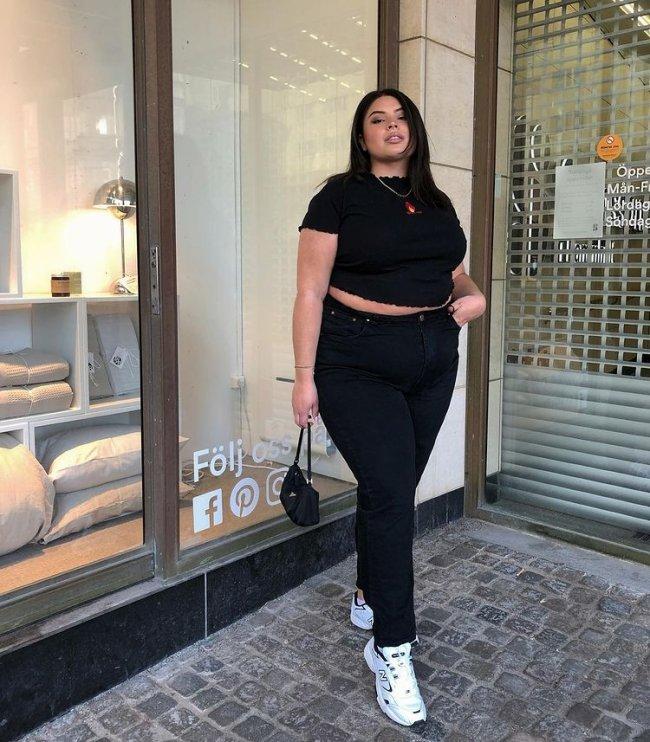 Foto de uma mulher na calçada. Ela usa uma blusa preta, calça skinny preta, bolsa preta e tênis branco. Ela olha para a câmera e não sorri.
