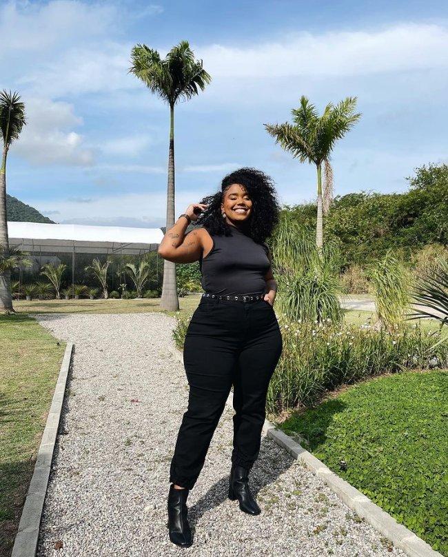 Foto de uma mulher na rua. Ela usa uma regata preta, calça preta skinny e bota. Ela olha para a câmera e sorri.