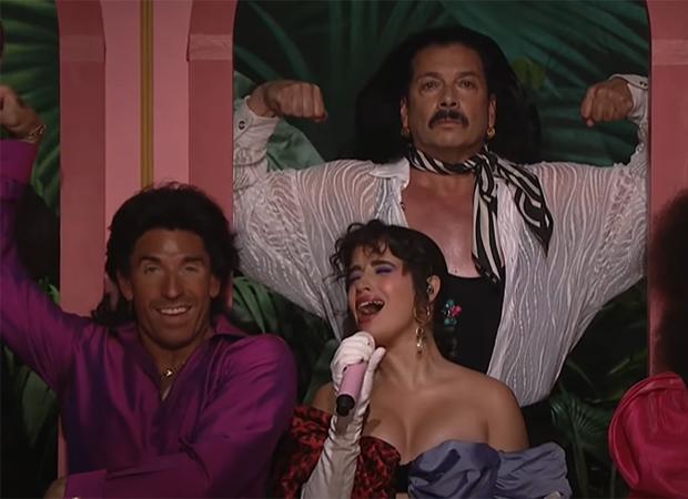 Camila Cabello cantando com microfone na mão. Ela tem dançarino ao seu lado e outro atrás dela