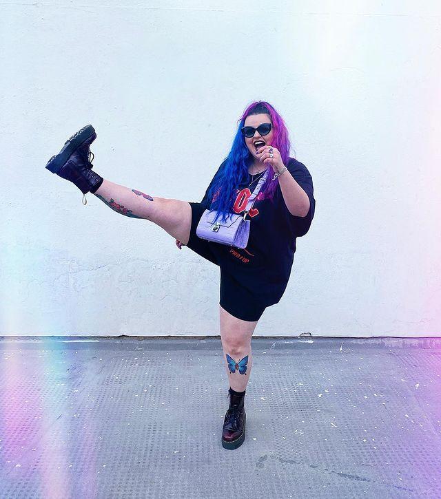 Jovem fazendo pose com uma perna levantada, com cabelo colorido usando óculos escuro em fundo branco.
