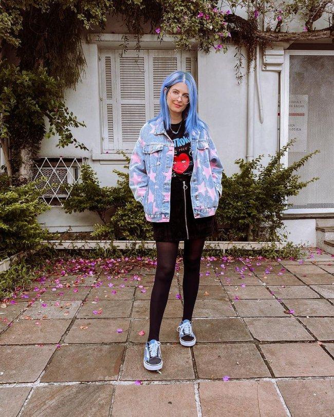 Jovem posando em frente a sua casa, com jaqueta, saia, meia calça, tênis e camiseta de banda. Ela está com as duas mãos dentro dos bolsos da jaqueta e aparece com uma expressão sorridente.