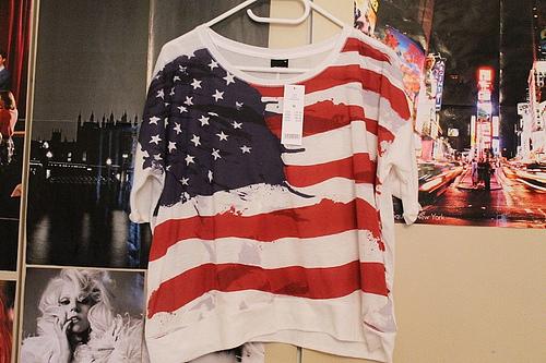 Foto de uma camiseta com estampa dos Estados Unidos pendurada em um cabide na parede de um quarto.
