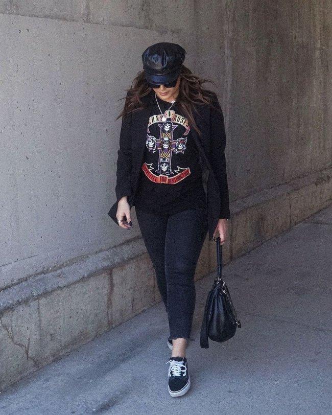 Jovem olhando para baixo usando boina preta, calça preta e segurando bolsa da mesma cor.