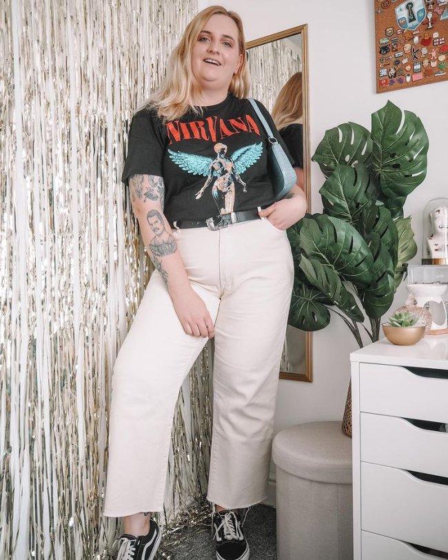 Jovem com calça branca, e camiseta de banda apoiada na parede com expressão divertida. Ela é loira e está ao lado e sua cômoda e uma planta verde.