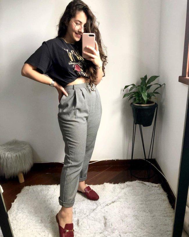 Jovem tirando foto no espelho com planta ao lado, usando mocassim, calça cinza e camiseta de banda.