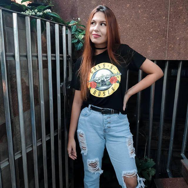 Jovem posando com camiseta de banda, mão na cintura, expressão sorridente calça jeans.