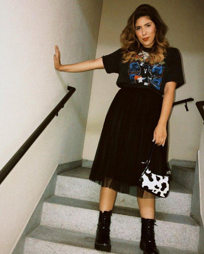 Jovem posando em uma escada com saia preta, camiseta de banda e bolsa com estampa de vaca.