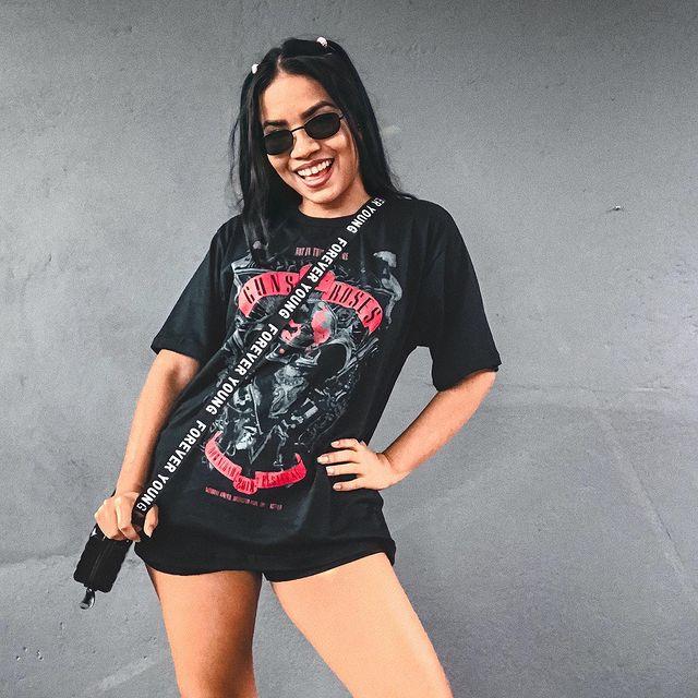 Jovem posando com o corpo levemente inclinado para o lado direito e uma das mãos na cintura, ela usa camiseta de banda, short preto e óculos escuros.