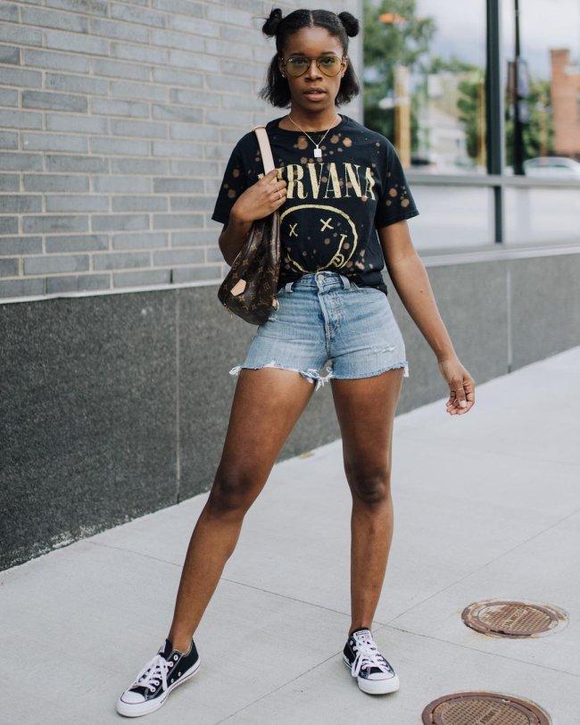 Jovem posando com short jeans e camiseta de banda. Sua expressão é séria e ela usa o penteado space buns em seus cabelos.