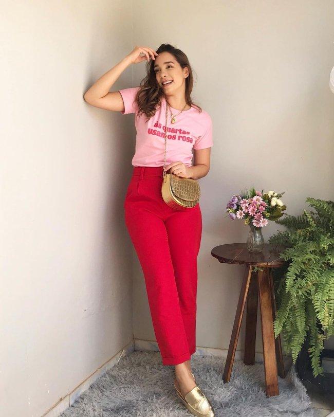 Jovem posando encostada na parede branca usando camiseta rosa com calça vermelha ao lado de plantas verdes e em um banco de madeira marrom.
