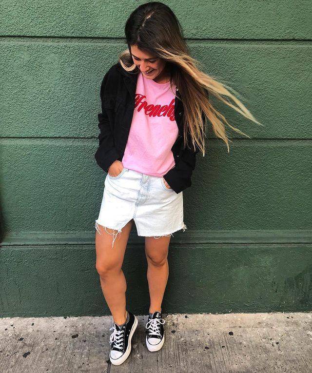 Jovem posando em porta verde enquanto olha para baixo, ela usa casaco preto, saia branca e camiseta rosa com palavra em vermelho.