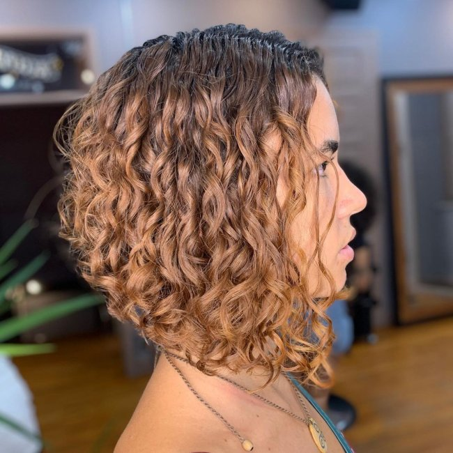 Foto de uma mulher de perfil mostrando o corte chanel de bico em seu cabelo ondulado.