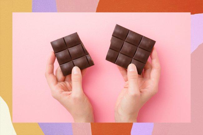 Uma mão segurando um tablete de chocolate amargo sobre um fundo rosa