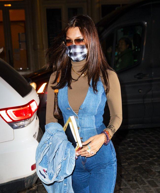 Foto da modelo Bella Hadid na rua. Ela usa uma calça jeans, blusa marrom e colete jeans, colete jeans como sobreposição, bolsa baguete marrom, colar dourado, óculos de sol e máscara facial quadriculada. Ela olha para frente e não sorri para a foto.