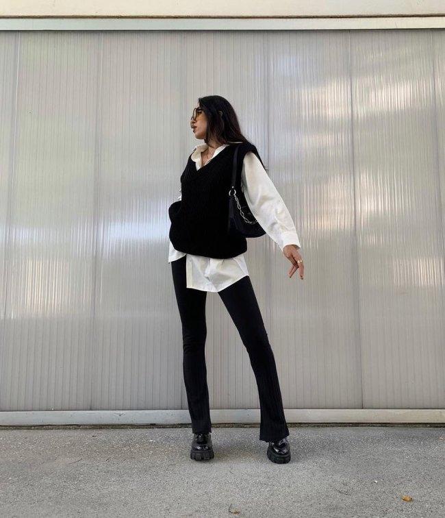 Jovem posando olhando para trás, com camisa branca e colete preto e calça bailarina.