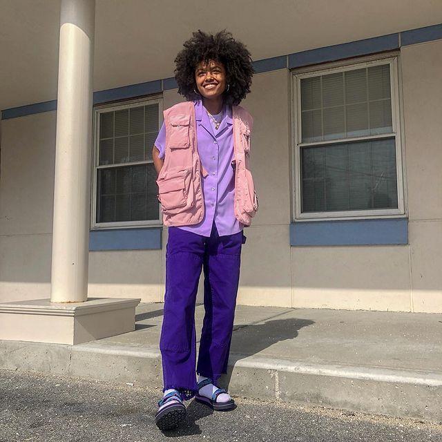 Foto de uma mulher em uma escada. Ela usa uma camiseta lilás, colete cargo rosa claro, calça azul, meia e papete. Ela está com as mãos nos bolsos do colete, olha para frente e sorri.