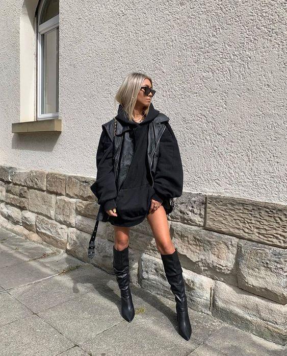 Foto de uma mulher na rua. Ela usa uma blusa de moletom preta oversized como vestido, bota preta modelo over the knee, bolsa preta, colete de couro preto como sobreposição, óculos escuros e cabelo solto. Ela olha para o lado e não sorri.