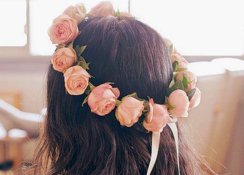 Foto do cabelo de uma menina com uma coroa de flores rosa.