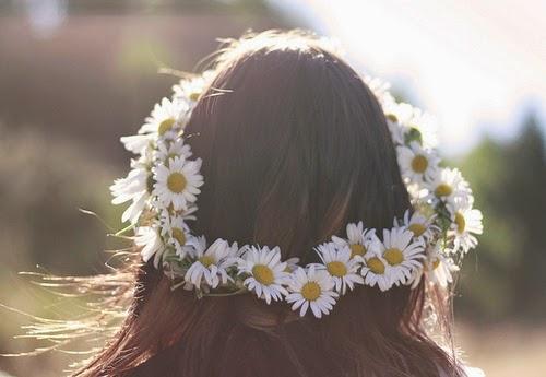 Foto do cabelo de uma garota com coroa de flores. As flores são margaridas.