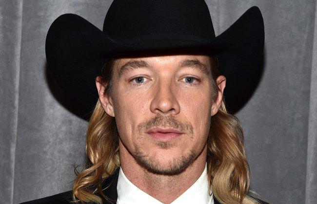 Foto do DJ Diplo. Ele tem cabelo loiro e longo, e veste um chapéu de cowboy preto