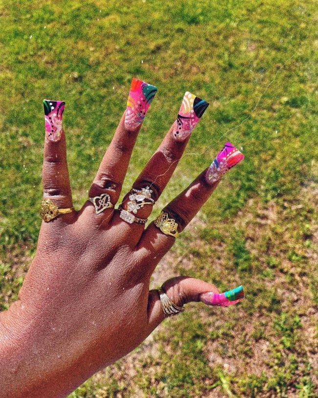 Foto com foco nas unhas com formato duck feet. As unhas estão esticadas. E tem desenhos irregulares na cor rosa, preto e verde.