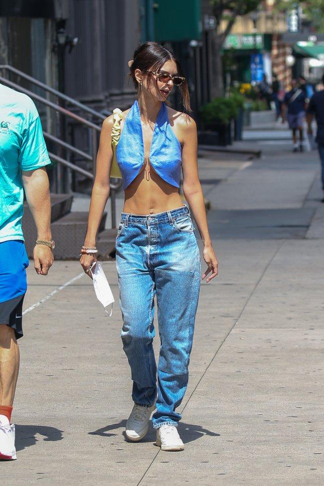 Foto da modelo Emily Ratajkowski na rua. Ela usa um top azul com detalhe de alfinete no decote, calça jeans, tênis branco e cabelo preso em um coque. Ela não olha para a câmera e não sorri.