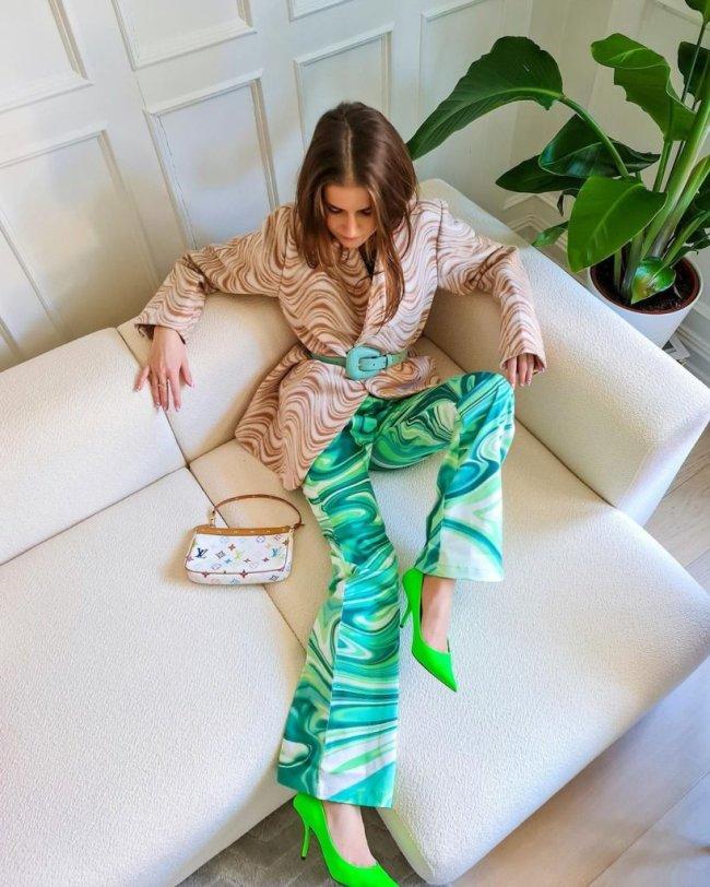 Jovem sentada em sofá branco com uma das pernas em cima dele, ela usa calça verde com detalhes psicodélicos e salto alto verde.