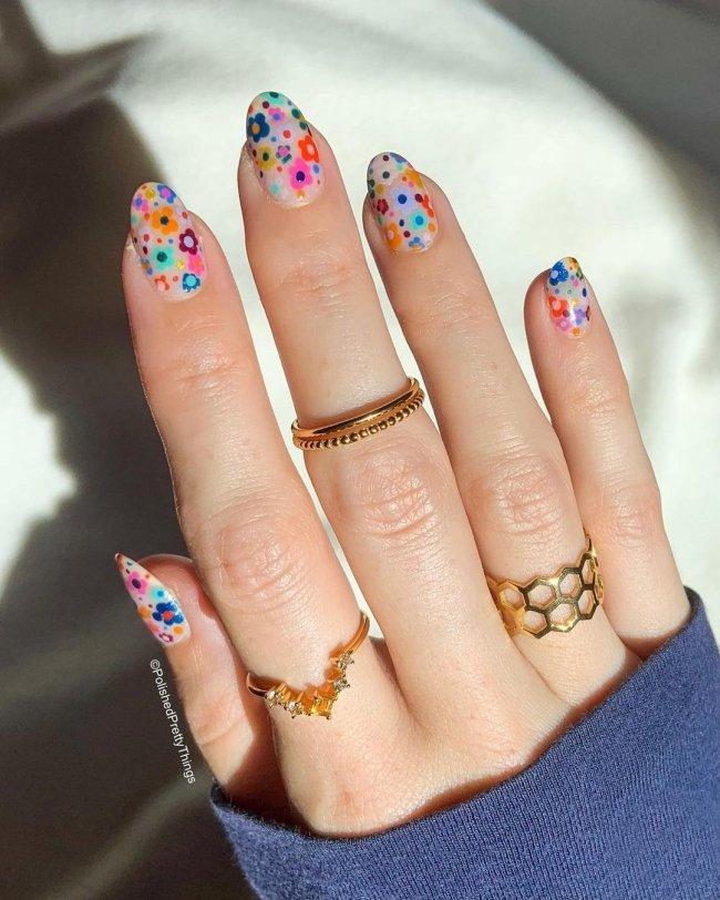 Foto com close nas unhas e tem nail art com desenho de flores coloridas, nas cores rosa, verde, laranja, azul e roxo.