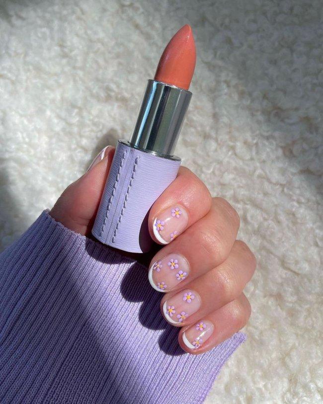 Foto com close nas unhas e tem nail art com francesinha branca e florzinha.