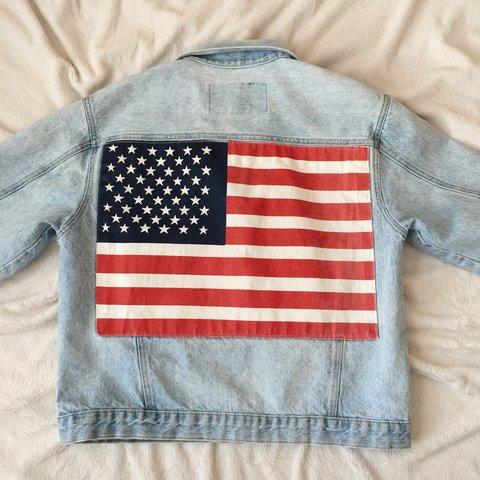 Foto de uma jaqueta jeans com a estampa da bandeira dos Estados Unidos nas costas.