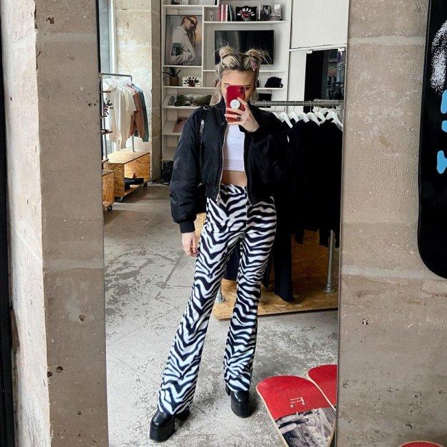 Jovem tirando foto do seu look em frente a espelho. Ela usa jaqueta preta, top branco e calça de zebra.