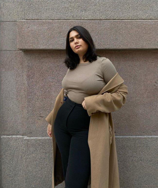 Foto de uma mulher na rua. Ela usa uma camiseta bege, casaco bege e calça skinny preta. Ela olha para a câmera e não sorri.