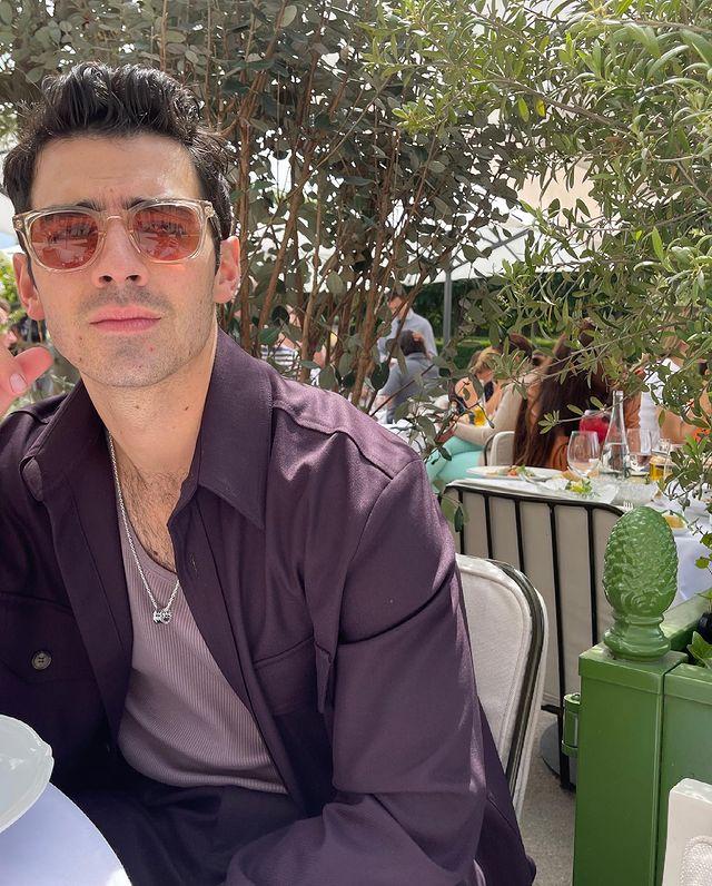 Joe Jonas olhando para algo atrás da câmera; ele usa uma camiseta lilás com uma camisa roxa por cima e óculos de sol com lente vermelha; sua expressão é confusa