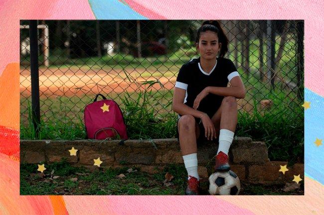 A jogadora de futebol Kezia Sousa está sentada ao lado de um campo, com uma bola embaixo do pé