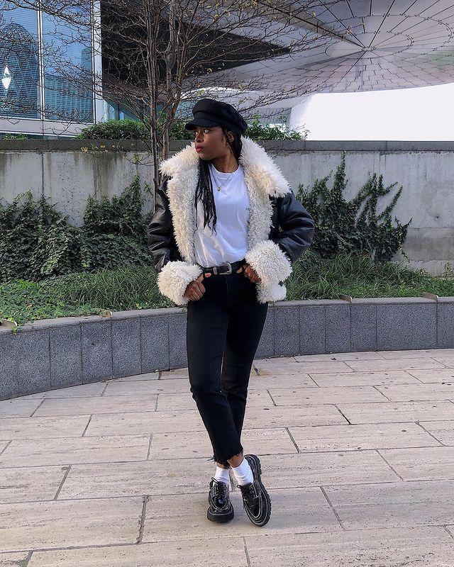 Foto de uma mulher em uma calçada. Ela usa uma boina preta, camiseta branca, casaco de pelinho branco e preto, calça skinny preta, cinto preto e mocassim preto. Ela olha para o lado e não sorri.