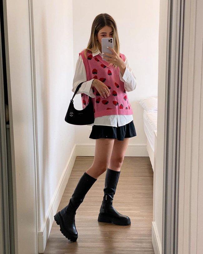 Selfie no espelho de uma mulher. Ela usa uma camisa branca, colete de vovô rosa com estampa de morangos como sobreposição, saia preta, coturno preto e bolsa preta. Ela olha para a tela do celular e não sorri.