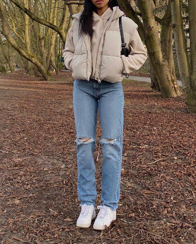Foto do look de uma garota. Ela usa uma blusa de moletom bege, colete puffer bege, calça jeans e tênis branco. Ela está com as duas mãos no bolso do colete e não é possível ver o rosto dela na foto.