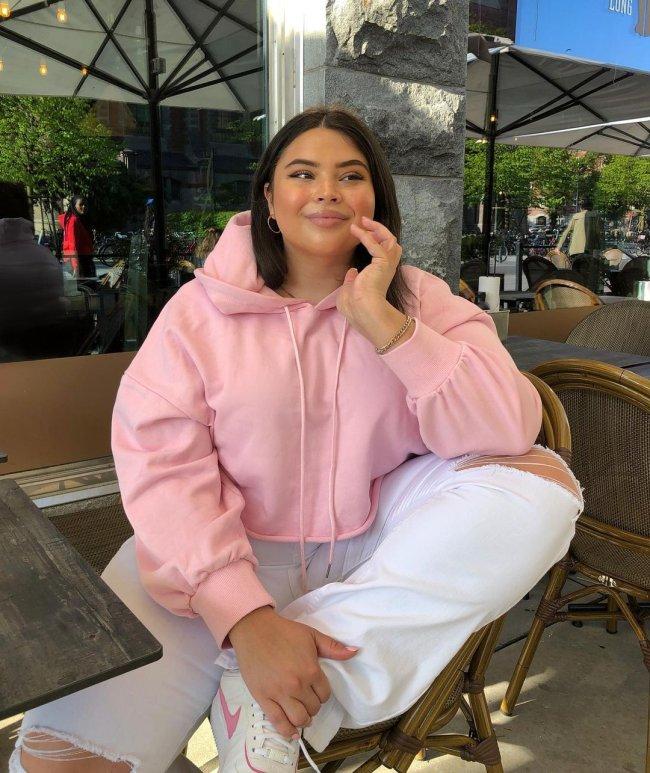 Foto de uma mulher sentada em uma mesa de restaurante. Ela usa uma blusa de moletom com capuz rosa, calça jeans branca e tênis branco. Ela apoia a mão esquerda no queixo e a segura a perna esquerda com a mão direita, olha para o lado e sorri levemente.