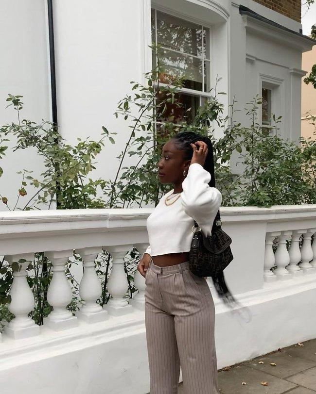 Foto de uma mulher na calçada. Ela usa um moletom branco no modelo cropped, calça de alfaiataria listrada e bolsa preta. Ela está com o cabelo preso em um rabo de cavalo, com a mão esquerda na cabeça, olha para o lado e não sorri.