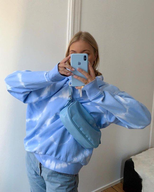 Selfie no espelho de uma mulher. Ela usa um moletom tie dye azul, calça jeans e bolsa azul.