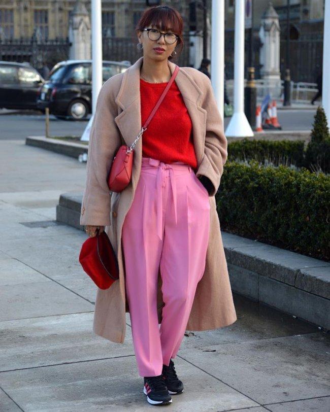 Jovem posando para foto na rua usando blazer bege e camisa vermelha com calça rosa, ela está com uma das mãos no bolso e a outra segura uma bolsa vermelha.
