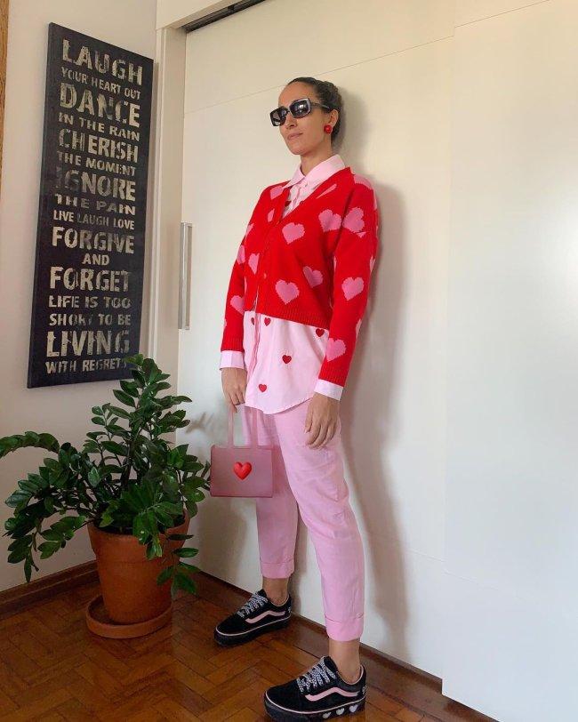 Jovem encostada na parede usando casaco vermelho, camisa rosa e calça rosa. Sua expressão é séria. Podemos ver um vaso de planta ao lado dela e um quadro preto com frases escritas na cor branca.