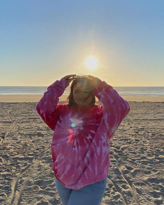 Foto de uma mulher na praia. Ela usa um moletom tie dye rosa, calça jeans e óculos de sol na cabeça. Ela segura o óculos de sol no topo da cabeça com as duas mãos, olha para a câmera e sorri levemente.