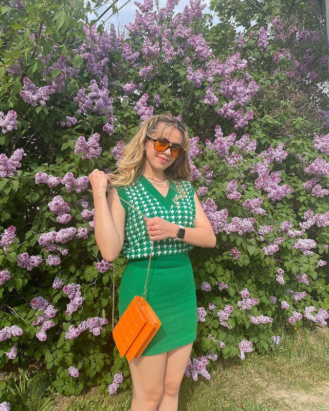 Garota usando colete de tricô sem alças verde e saia no mesmo tom, além de um óculos de sol de lentes alaranjadas e uma bolsa laranja neon, que está sendo segurada pelas suas duas mãos. Ao fundo dela, há várias flores roxas.